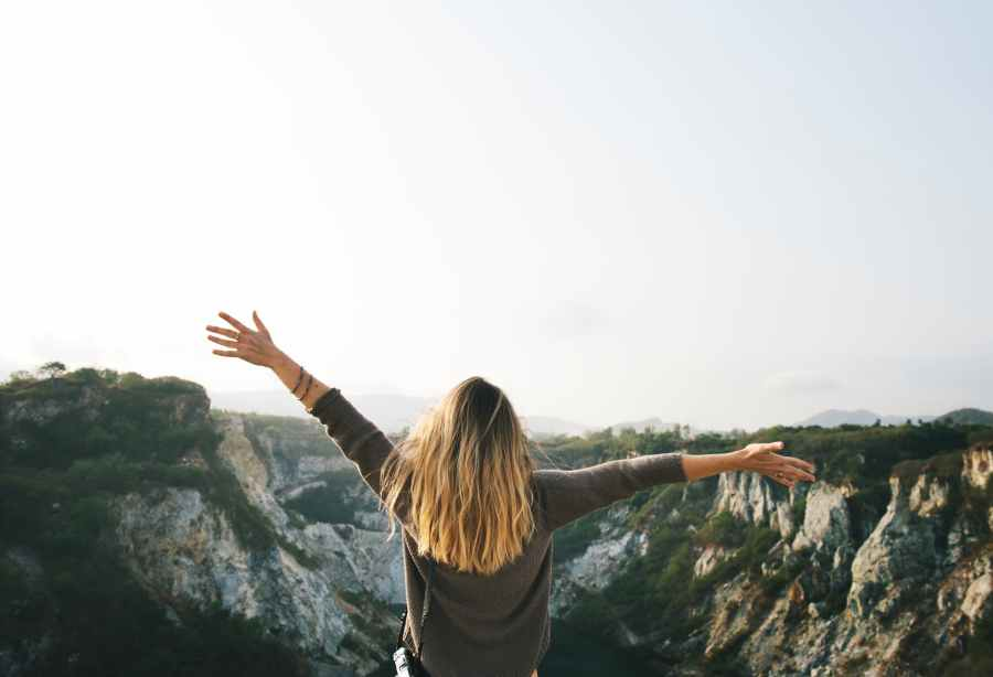 woman with blonde hair at the top of the mountain raising her hands