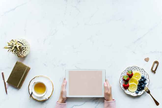 person holding white tablet computer beside teacup and saucer of blueberries