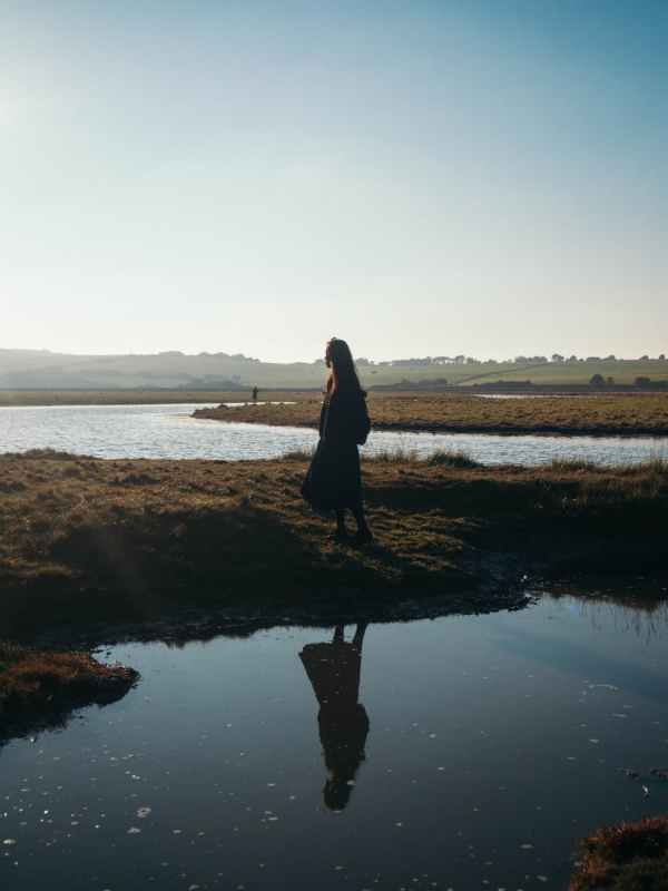 woman standing near body of water